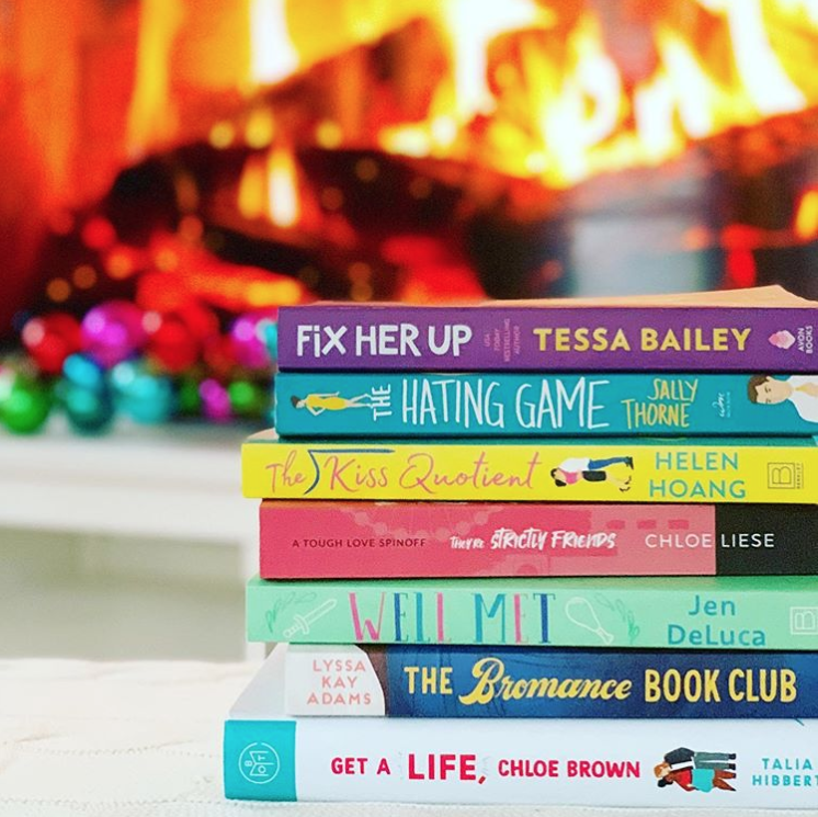Pile of colorful romance novels in front of a warm, likely fireplace