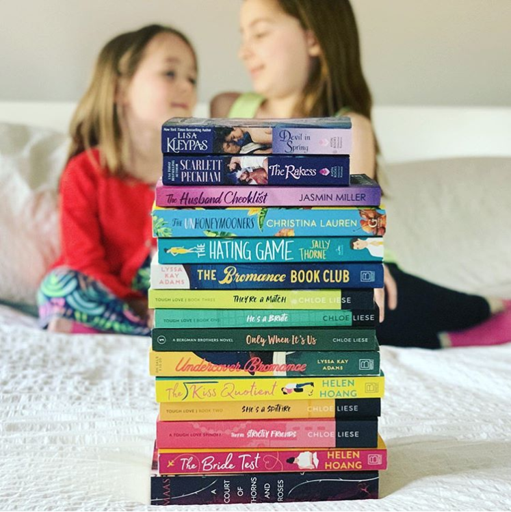 Photo of a stack of colorful romance novels on a white bedspread with two young girls in the background.