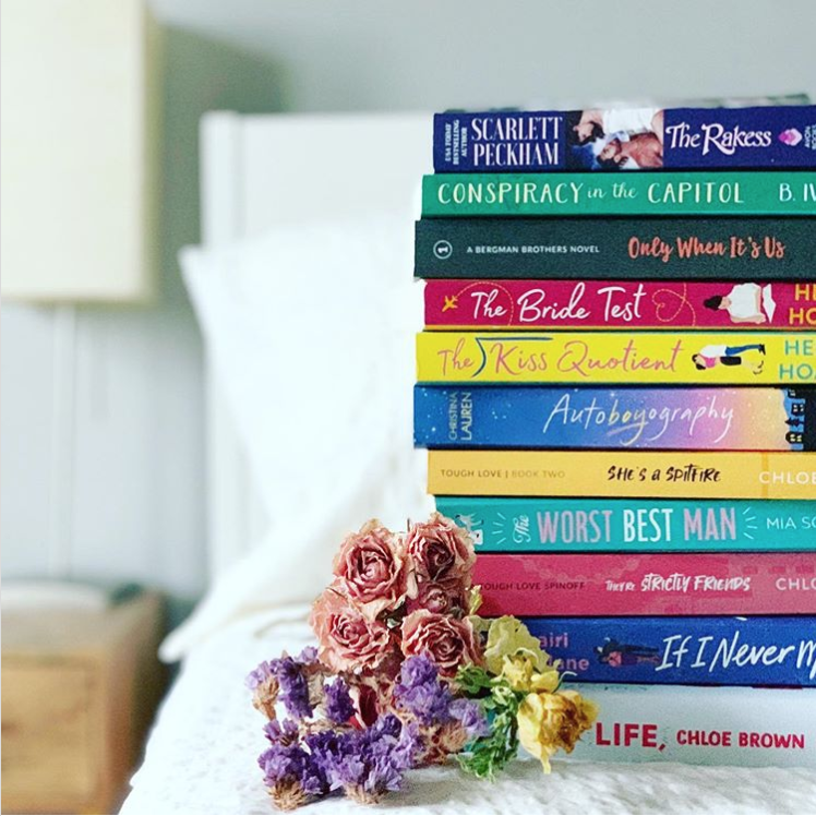 Stack of brightly colored romance novels on a white bed with a small wooden nightstand in the background.